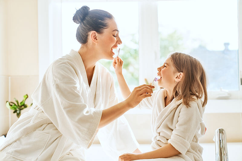 Mother and her young daughter brushing each other's teeth