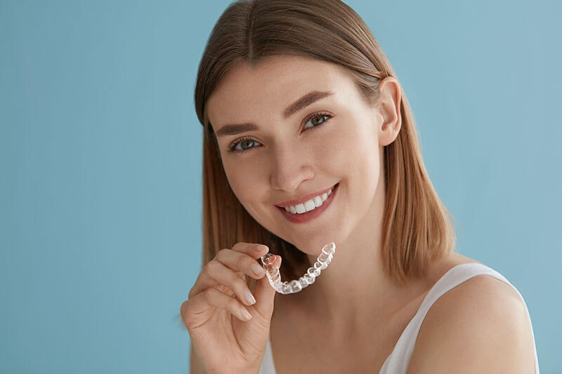 Young woman smiling and holding Invisalign aligners